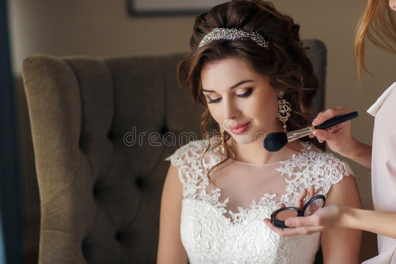 Όμορφη νύφη στη συνεδρίαση γαμήλιων φορεμάτων σε μια καρέκλα στο δωμάτιο ξενοδοχείου στοκ φωτογραφίες