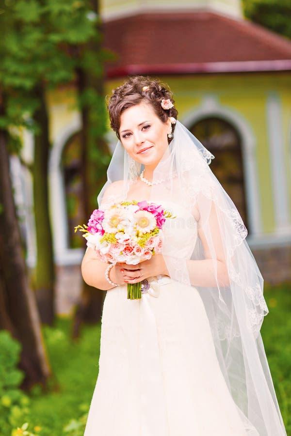 Όμορφη νύφη στον άσπρο γάμο εκμετάλλευσης φορεμάτων στοκ φωτογραφίες