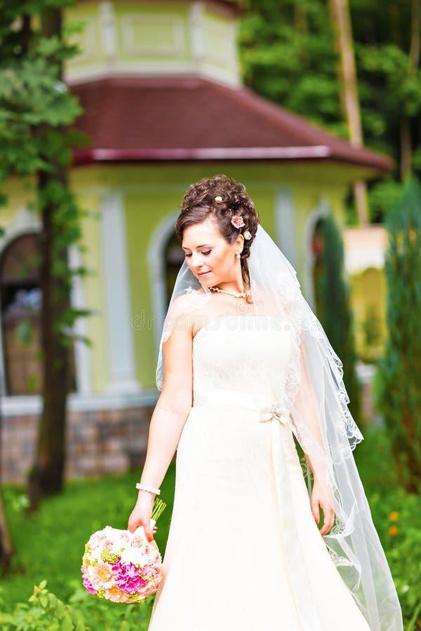 Όμορφη νύφη στον άσπρο γάμο εκμετάλλευσης φορεμάτων στοκ φωτογραφία με δικαίωμα ελεύθερης χρήσης