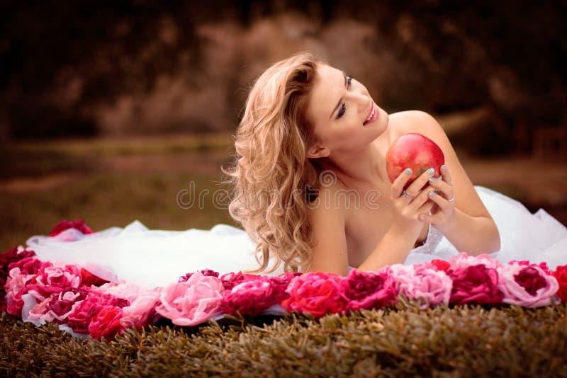 Όμορφη νύφη στο άσπρο φόρεμα με τα ρόδινα και κόκκινα λουλούδια, πάρκο στοκ εικόνες
