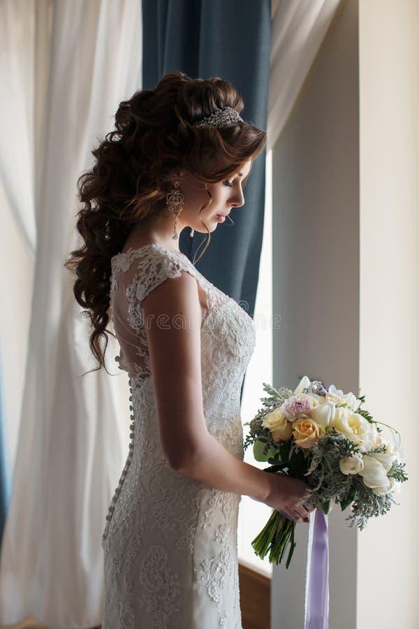 Όμορφη νύφη στο γαμήλιο φόρεμα με την ανθοδέσμη των λουλουδιών στοκ εικόνα με δικαίωμα ελεύθερης χρήσης