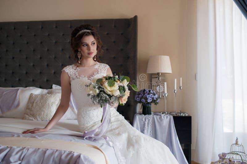 Όμορφη νύφη στο γαμήλιο φόρεμα με την ανθοδέσμη των λουλουδιών στοκ εικόνα