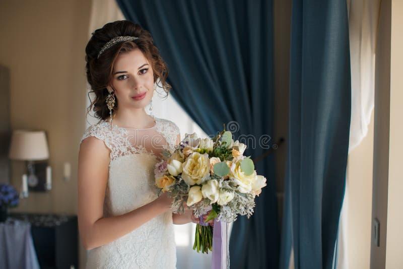Όμορφη νύφη στο γαμήλιο φόρεμα με την ανθοδέσμη των λουλουδιών στοκ φωτογραφίες