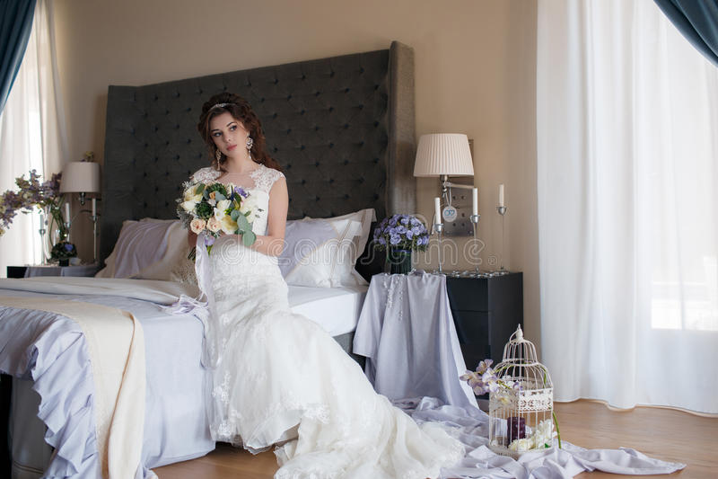 Όμορφη νύφη στο γαμήλιο φόρεμα με την ανθοδέσμη των λουλουδιών στοκ εικόνες