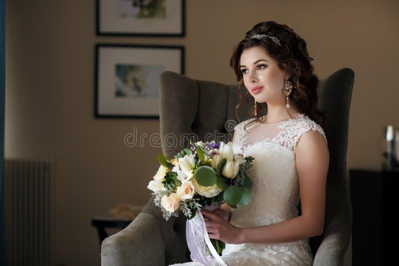 Όμορφη νύφη στο γαμήλιο φόρεμα με την ανθοδέσμη των λουλουδιών στοκ φωτογραφία