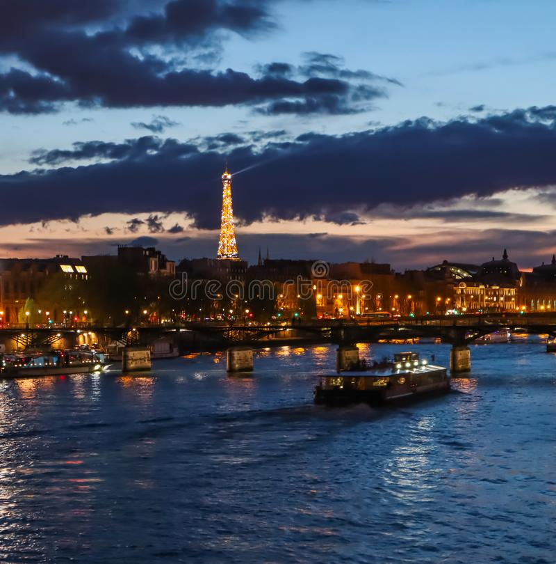 Όμορφη νύχτα Παρίσι, λαμπιρίζοντας πύργος του Άιφελ, γέφυρα Pont des Arts πέρα από τον ποταμό Σηκουάνας και τουριστικές βάρκες Γα στοκ φωτογραφίες