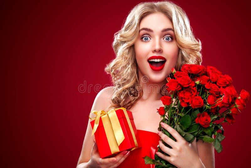 Όμορφη ξανθή ανθοδέσμη εκμετάλλευσης γυναικών των κόκκινων τριαντάφυλλων και του δώρου Βαλεντίνος Αγίου και διεθνής ημέρα γυναικώ στοκ φωτογραφία