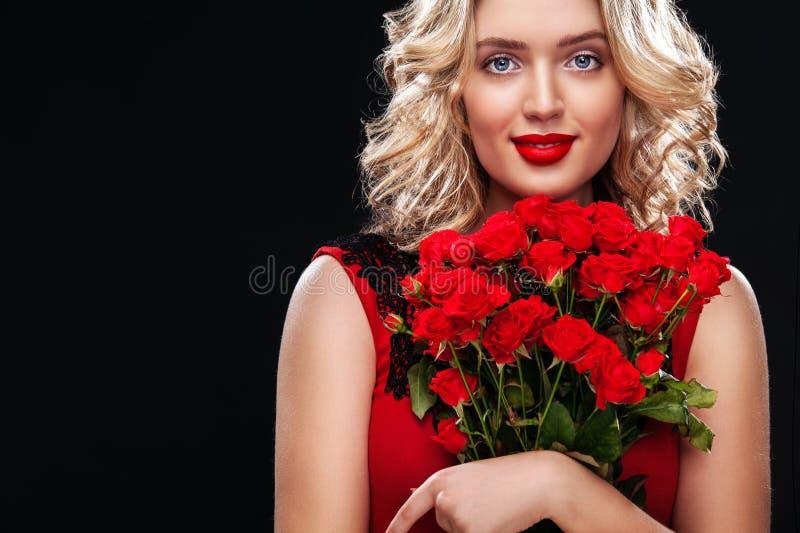 Όμορφη ξανθή ανθοδέσμη εκμετάλλευσης γυναικών των κόκκινων τριαντάφυλλων Διεθνής ημέρα γυναικών ` s, οκτώ εορτασμός Μαρτίου στοκ εικόνα με δικαίωμα ελεύθερης χρήσης