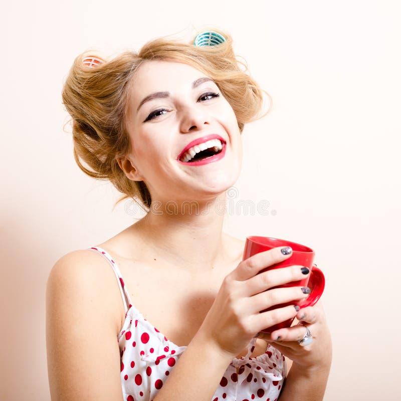 Όμορφη ξανθή αστεία pinup ξανθή γυναίκα ματιών κοριτσιών πράσινη με το ευτυχές χαμόγελο ρόλερ που εξετάζει το τσάι κατανάλωσης καμ στοκ φωτογραφίες με δικαίωμα ελεύθερης χρήσης