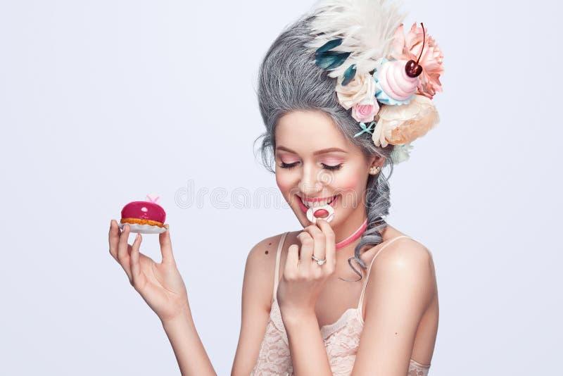 Όμορφη ξανθή γυναίκα με ένα κέικ Γλυκιά προκλητική κυρία κόκκινος τρύγος ύφους κρίνων απεικόνισης η μόδα σεντονιών βάζει τις σαγη στοκ φωτογραφία