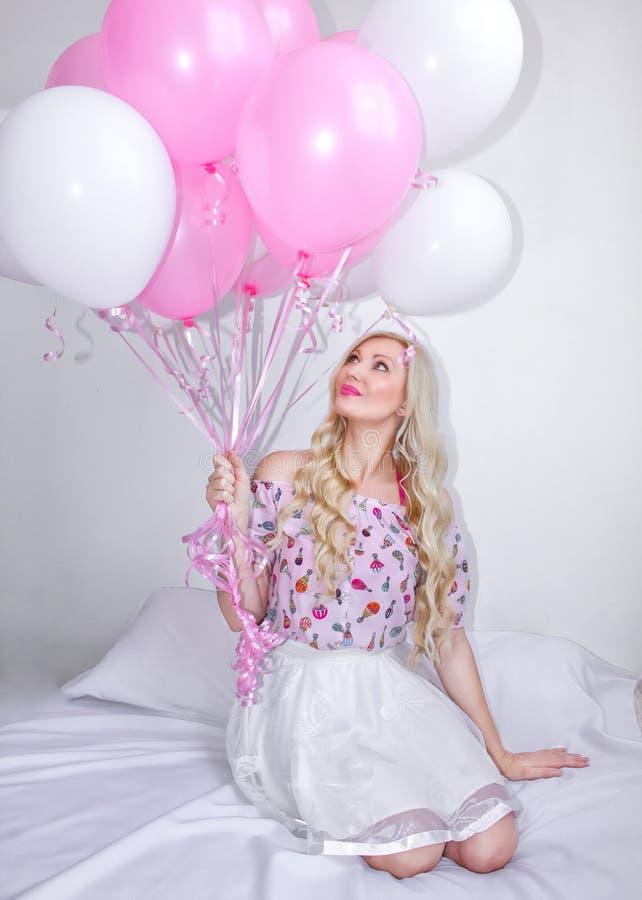 Όμορφη ξανθή γυναίκα με τα ρόδινα και άσπρα μπαλόνια συγκινήσεις χαρούμενε&sigm Εορτασμός Όμορφος ένας ξανθός κάθεται σε ένα κρεβ στοκ εικόνες