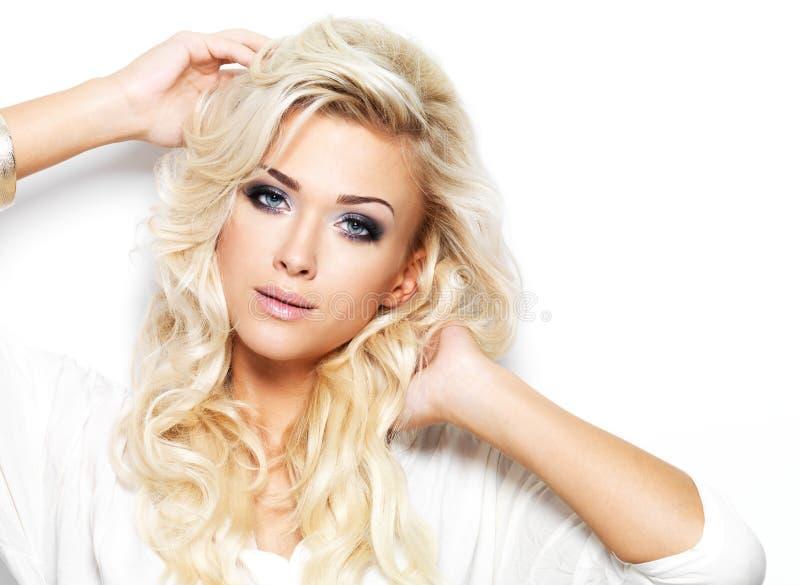 Όμορφη ξανθή γυναίκα με τη μακροχρόνια σγουρή τρίχα και το ύφος makeup στοκ φωτογραφία