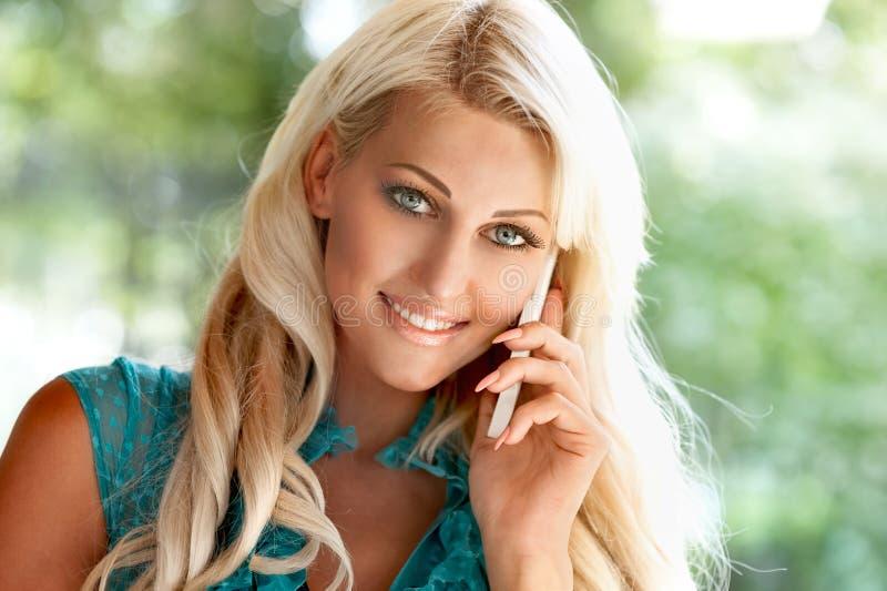 Όμορφη ξανθή γυναίκα με το τηλέφωνο κυττάρων στοκ εικόνα