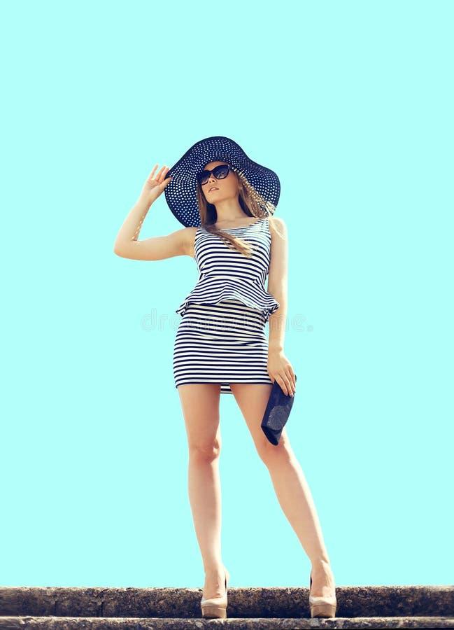 Όμορφη ξανθή γυναίκα μόδας που φορά το ριγωτό φόρεμα, καπέλο αχύρου στοκ εικόνες