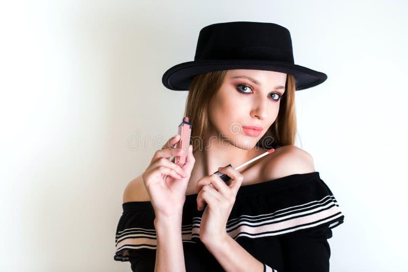 Όμορφη ξανθή γυναίκα, ομορφιά blogger στο κραγιόν λαβής μαύρων καπέλων υπό εξέταση Τα καλλυντικά, χείλι σχολιάζουν, αντιμετωπίζου στοκ φωτογραφίες με δικαίωμα ελεύθερης χρήσης