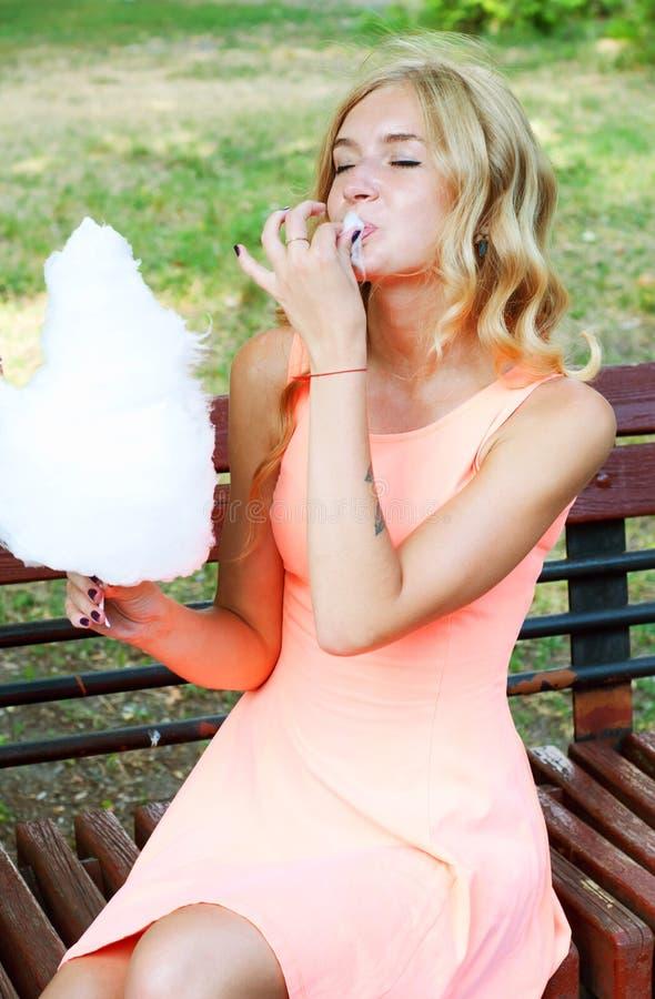 Όμορφη ξανθή γυναίκα που απολαμβάνει την καραμέλα βαμβακιού στοκ φωτογραφία