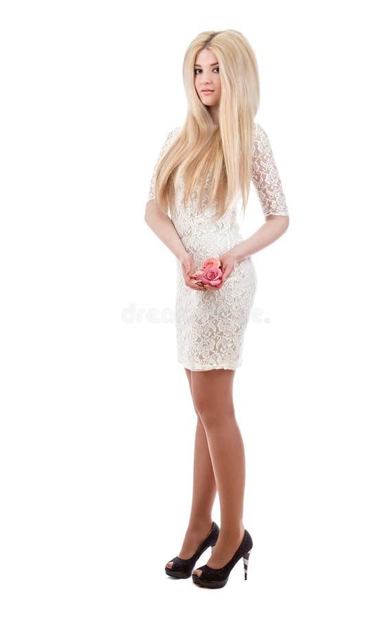 Όμορφη ξανθή γυναίκα που κρατά τα ρόδινα τριαντάφυλλα στοκ εικόνες