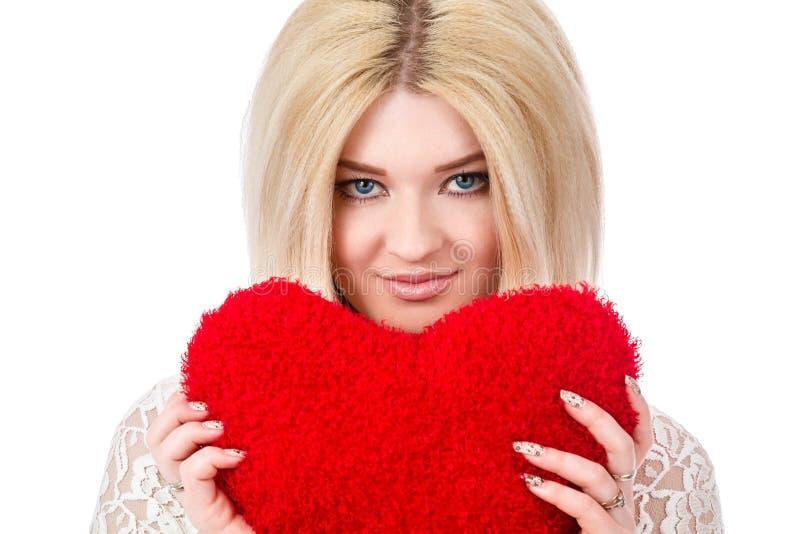 Όμορφη ξανθή γυναίκα που κρατά την κόκκινη καρδιά στοκ εικόνες