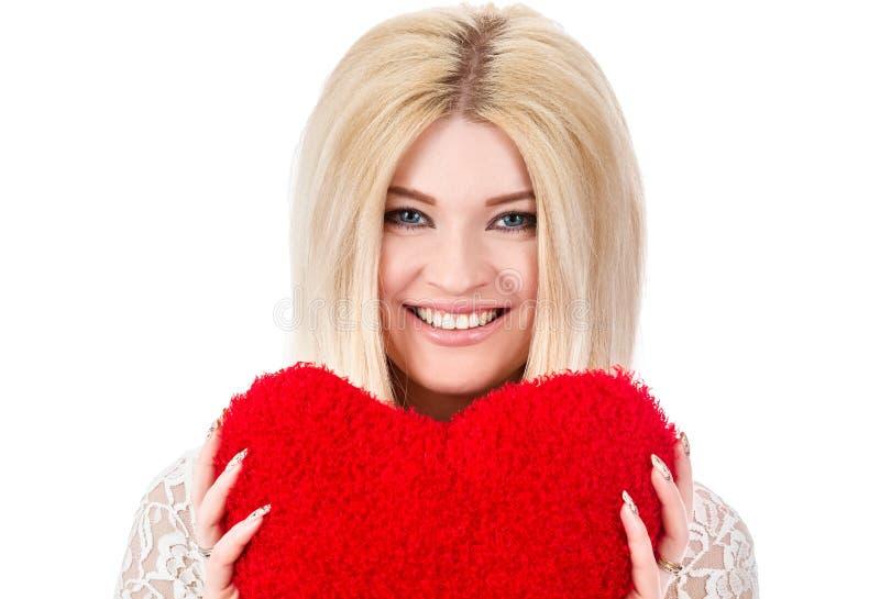 Όμορφη ξανθή γυναίκα που κρατά την κόκκινη καρδιά στοκ φωτογραφία