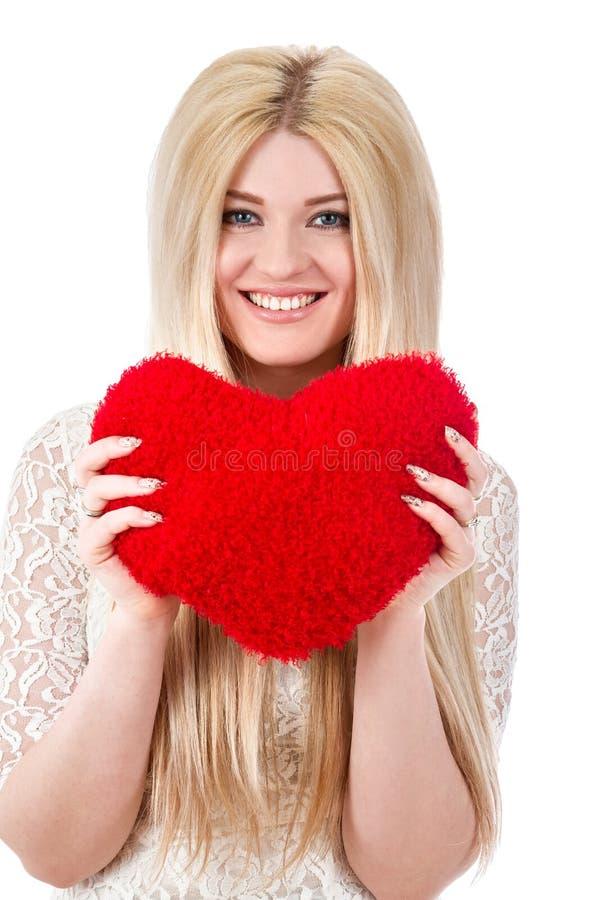 Όμορφη ξανθή γυναίκα που κρατά την κόκκινη καρδιά στοκ εικόνες με δικαίωμα ελεύθερης χρήσης