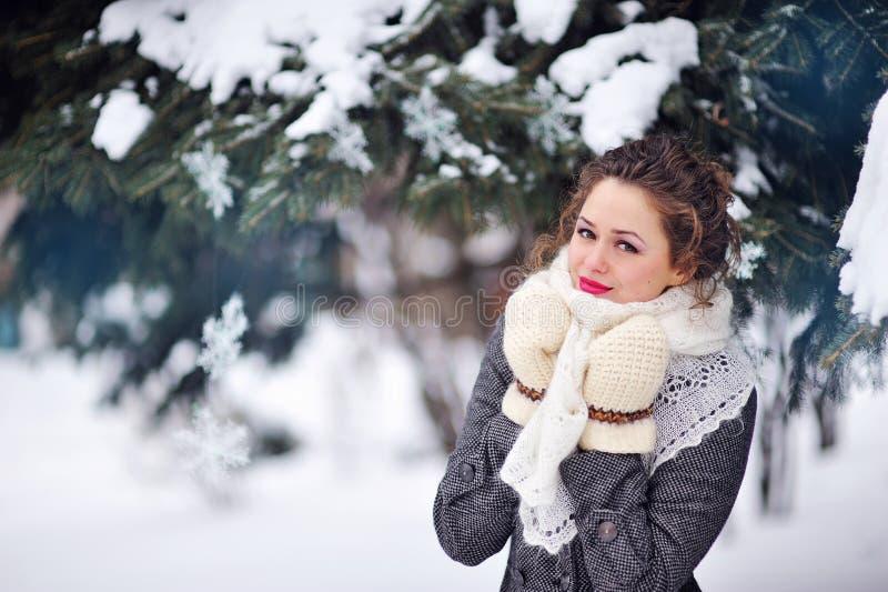 Όμορφη ξανθή γυναίκα που περπατά υπαίθρια κάτω από τις χιονοπτώσεις στοκ εικόνα