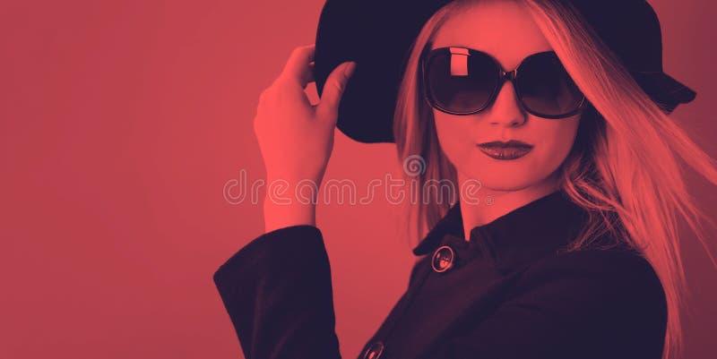 Όμορφη ξανθή γυναίκα σε ένα μαύρο παλτό στοκ εικόνα
