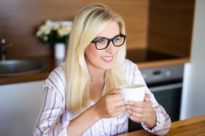 Όμορφη ξανθή γυναίκα στις πυτζάμες που πίνει τον καφέ στο σπίτι στοκ εικόνες