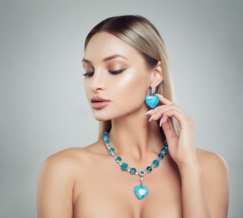 Όμορφη ξανθή γυναίκα στο περιδέραιο κοσμήματος και σκουλαρίκια με Dia στοκ εικόνες