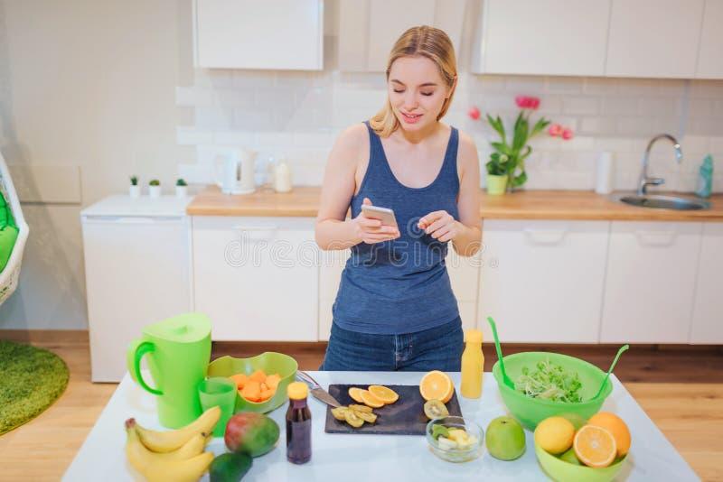 Όμορφη ξανθή γυναίκα Vegan με το smartphone που φωτογραφίζει το οργανικό πορτοκάλι στην κουζίνα τρόφιμα υγιή Διατροφή detox στοκ εικόνα με δικαίωμα ελεύθερης χρήσης