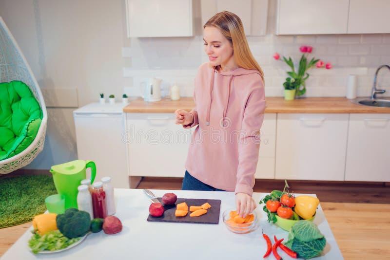 Όμορφη ξανθή γυναίκα Vegan που μαγειρεύει τα ακατέργαστα λαχανικά στην κουζίνα Χορτοφάγα τρόφιμα κατανάλωση υγιής Διατροφή Vegan στοκ εικόνα