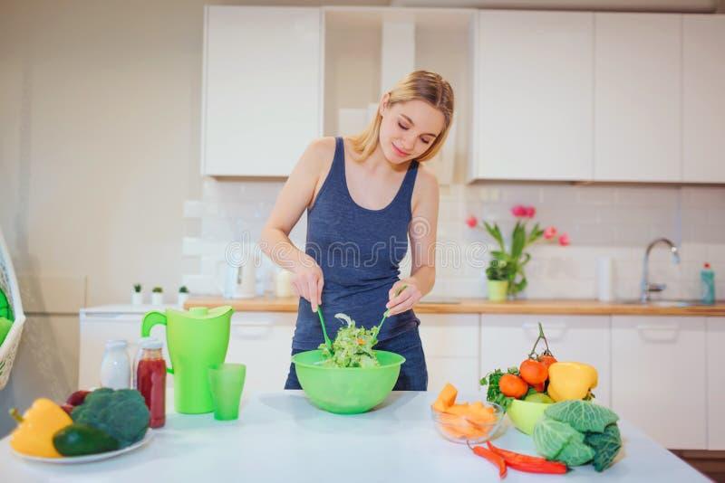 Όμορφη ξανθή γυναίκα Vegan που μαγειρεύει την εύγευστη σαλάτα στην κουζίνα Χορτοφάγα τρόφιμα κατανάλωση υγιής Διατροφή Vegan στοκ φωτογραφίες