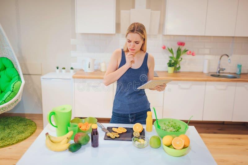 Όμορφη ξανθή γυναίκα Vegan που ψάχνει μια συνταγή στην ταμπλέτα για το μαγείρεμα των οργανικών φρούτων στην κουζίνα τρόφιμα υγιή στοκ φωτογραφία με δικαίωμα ελεύθερης χρήσης