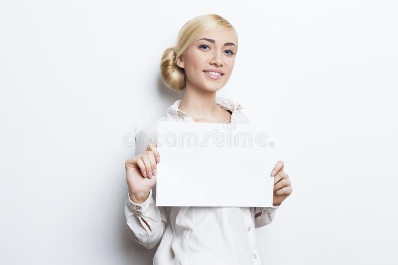 Όμορφη ξανθή επιχειρησιακή γυναίκα που κρατά το κενό έγγραφο στοκ φωτογραφία με δικαίωμα ελεύθερης χρήσης