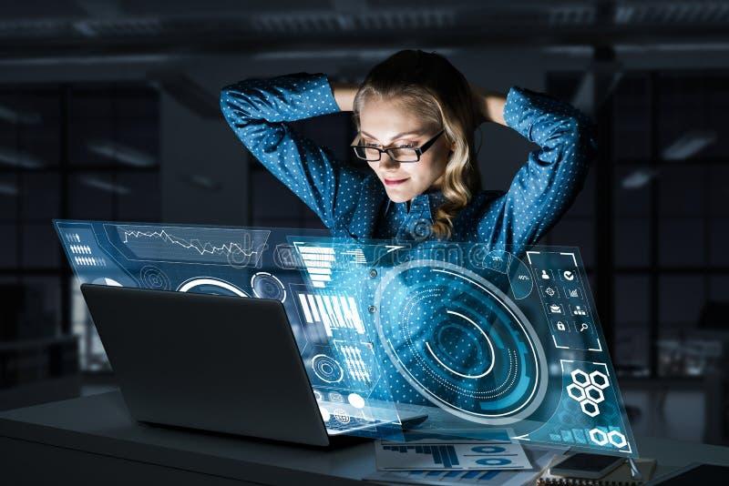 Όμορφη ξανθή εργασία στο lap-top και infographs από την οθόνη Μικτά μέσα στοκ εικόνα