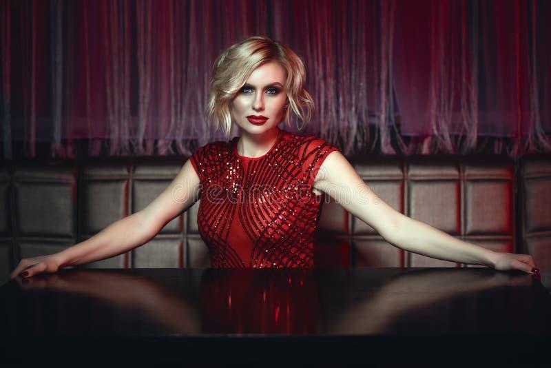 Όμορφη ξανθή κυρία στην κόκκινη συνεδρίαση φορεμάτων τσεκιών στον κενό πίνακα στη λέσχη νύχτας που περιμένει τη διαταγή στοκ φωτογραφία με δικαίωμα ελεύθερης χρήσης