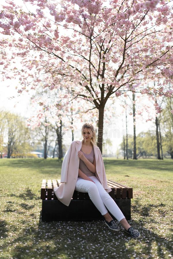 Όμορφη ξανθή νέα γυναίκα στο πάρκο ανθών κερασιών Sakura που απολαμβάνει την άνοιξη τη φύση και το ελεύθερο χρόνο κατά τη διάρκει στοκ φωτογραφία με δικαίωμα ελεύθερης χρήσης