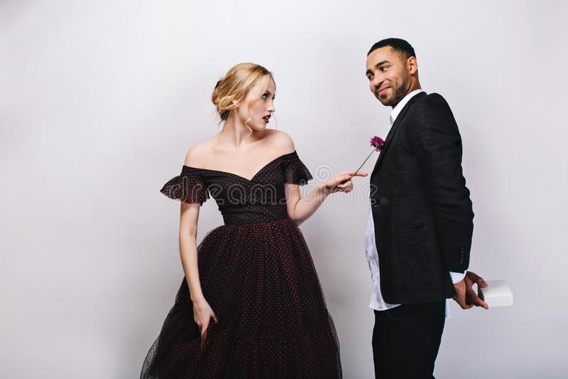 Όμορφη ξανθή νέα γυναίκα στο φόρεμα βραδιού πολυτέλειας που κοιτάζει discontentedly στον όμορφο φίλο στο σμόκιν στο λευκό στοκ φωτογραφία