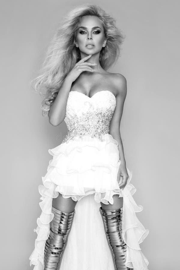 Όμορφη ξανθή νύφη σε ένα γαμήλιο φόρεμα και καταπληκτικά χρυσά παπούτσια στοκ εικόνα