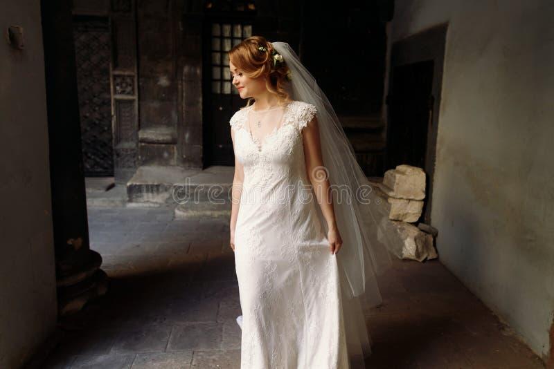 Όμορφη ξανθή νύφη στο κομψό άσπρο γαμήλιο φόρεμα που θέτει μέσα στοκ φωτογραφίες