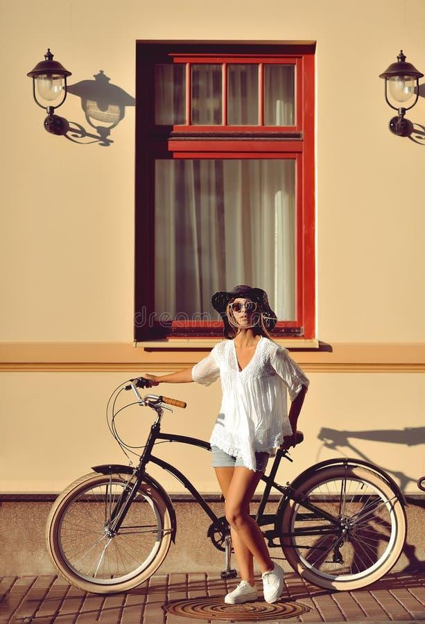 Όμορφη ξανθή στάση κοντά στο παλαιό ποδήλατό της fashion outdoor στοκ εικόνα με δικαίωμα ελεύθερης χρήσης