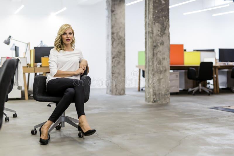 Όμορφη ξανθή συνεδρίαση επιχειρηματιών σε ένα γραφείο στοκ εικόνες με δικαίωμα ελεύθερης χρήσης