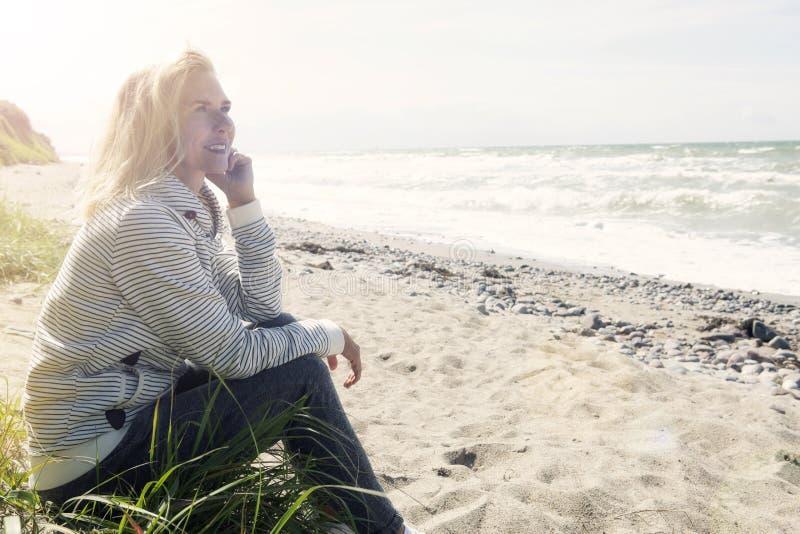 Όμορφη ξανθή συνεδρίαση γυναικών στην παραλία στοκ εικόνα με δικαίωμα ελεύθερης χρήσης