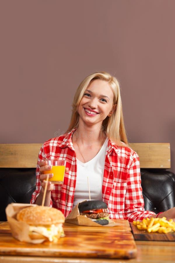 Όμορφη ξανθή συνεδρίαση γυναικών Burger βόειου κρέατος διαταγής χυμού από πορτοκάλι λαβής καφέδων που εξυπηρετείται στο έγγραφο γ στοκ φωτογραφίες με δικαίωμα ελεύθερης χρήσης