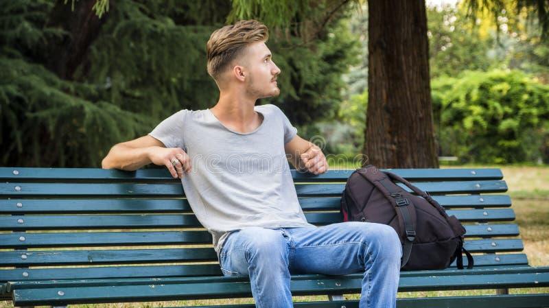 Όμορφη ξανθή συνεδρίαση νεαρών άνδρων στον πάγκο πάρκων στοκ φωτογραφία με δικαίωμα ελεύθερης χρήσης