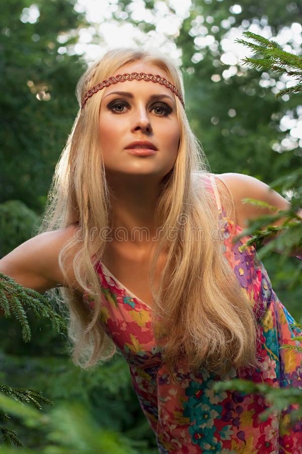 Όμορφη ξανθή τοποθέτηση γυναικών στο δάσος στοκ φωτογραφίες