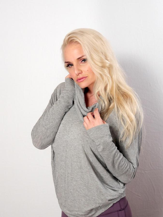 Όμορφη ξανθή τοποθέτηση ενάντια σε έναν άσπρο τοίχο, πρότυπο μόδας στοκ φωτογραφία