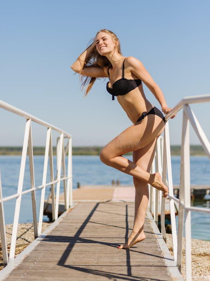 Όμορφη ξανθή χαλάρωση κοριτσιών σε ένα μαύρο μαγιό στο υπόβαθρο νερού Έννοια μόδας κολύμβησης στοκ φωτογραφία με δικαίωμα ελεύθερης χρήσης