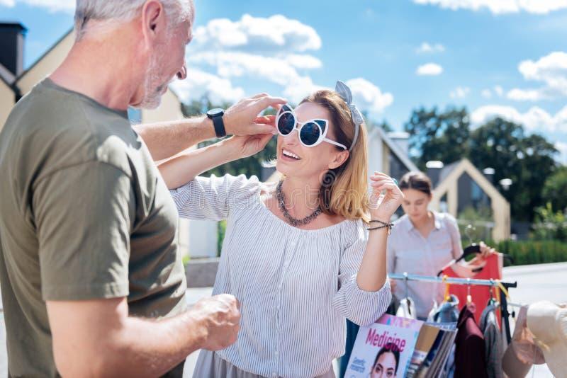 Όμορφη ξανθός-μαλλιαρή γυναίκα που φορά το συμπαθητικό περιδέραιο που δοκιμάζει τα γυαλιά ηλίου στοκ εικόνα