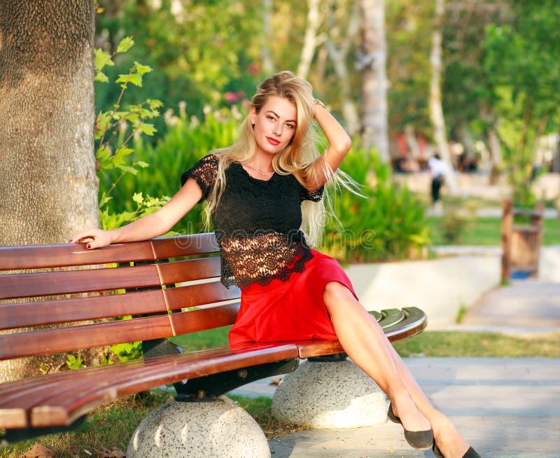 Όμορφη ονειροπόλος γυναίκα στον πάγκο στο πάρκο πόλεων το καλοκαίρι στοκ εικόνα