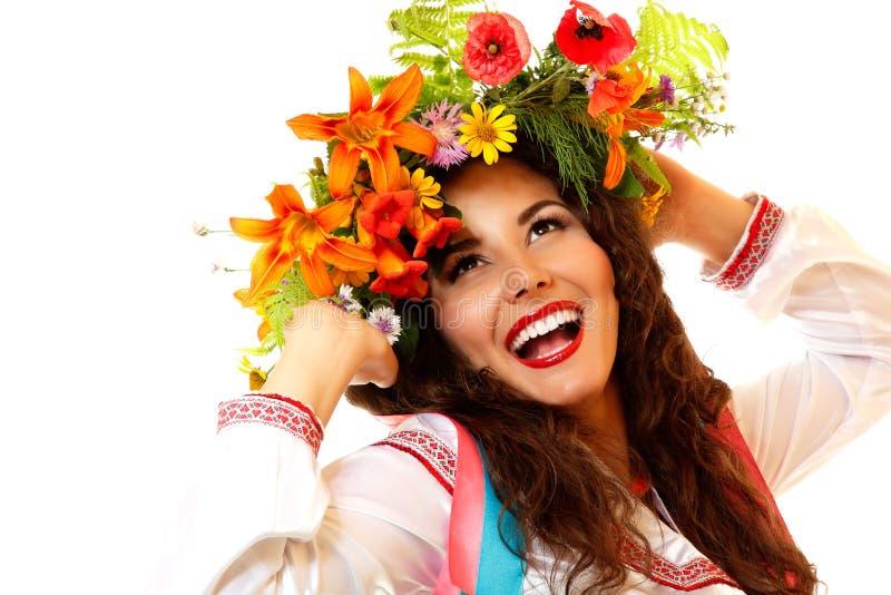 Όμορφη ουκρανική νέα γυναίκα στη γιρλάντα των θερινών λουλουδιών και στοκ φωτογραφίες
